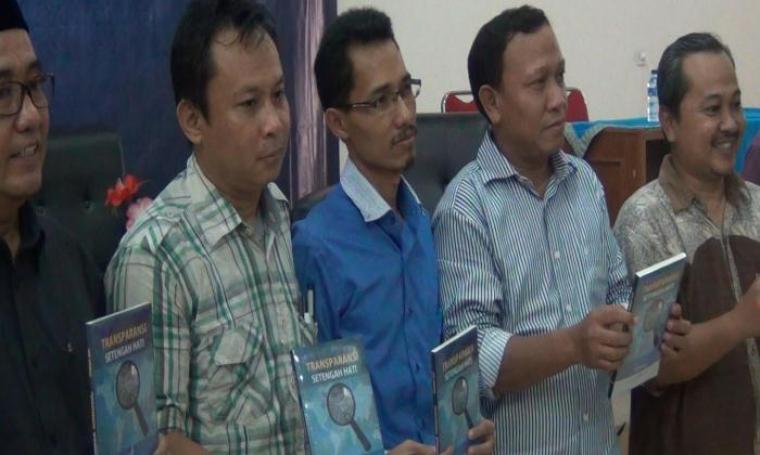 Komisioner Komisi Informasi (KI) Banten, Ade Jahran (tengah) saat menunjukan buku karya ketiganya. (Foto:TitikNOL)